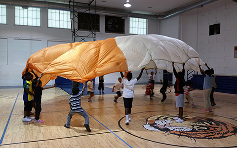 kids playing with parachute in gym