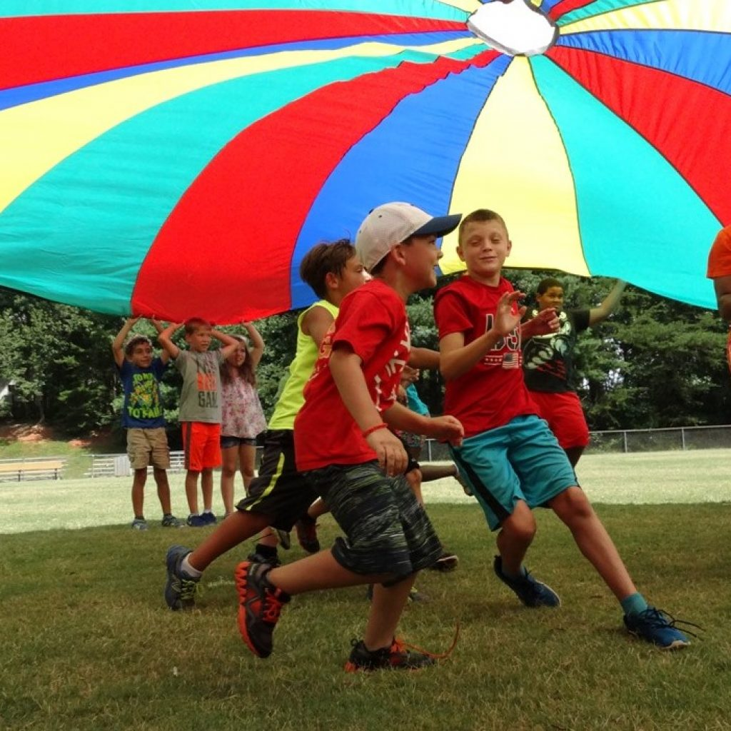 summer camp kids running under parachute