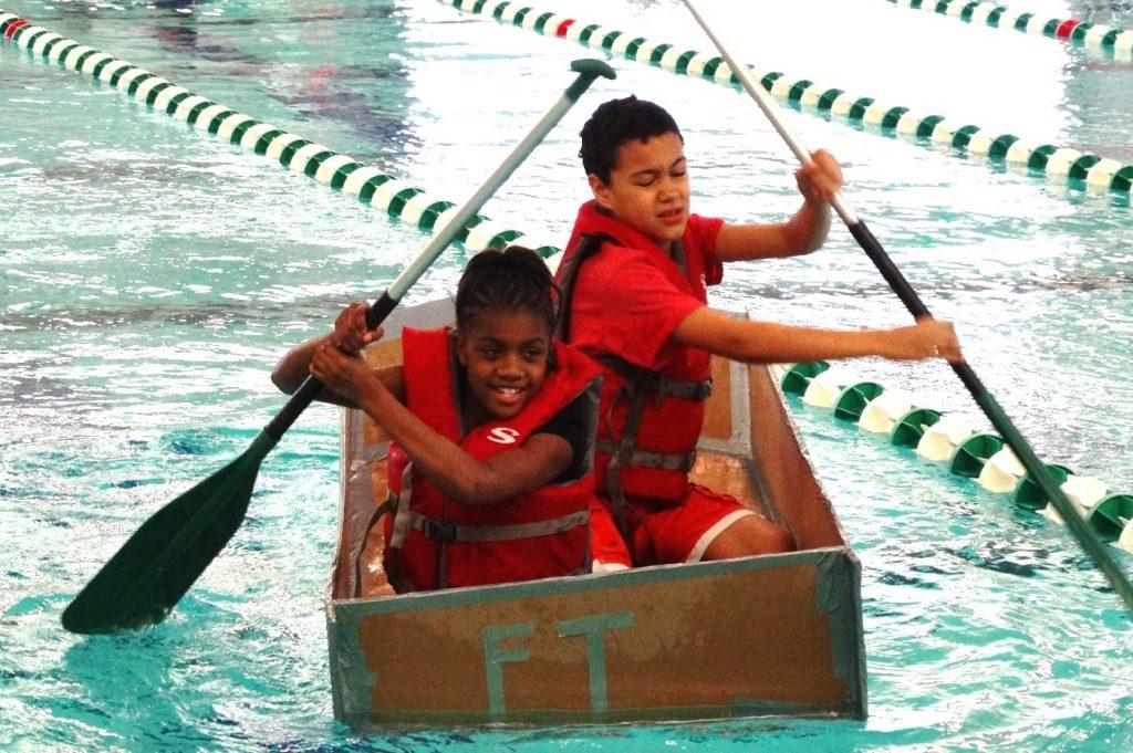 two kids paddling a cardboard boat