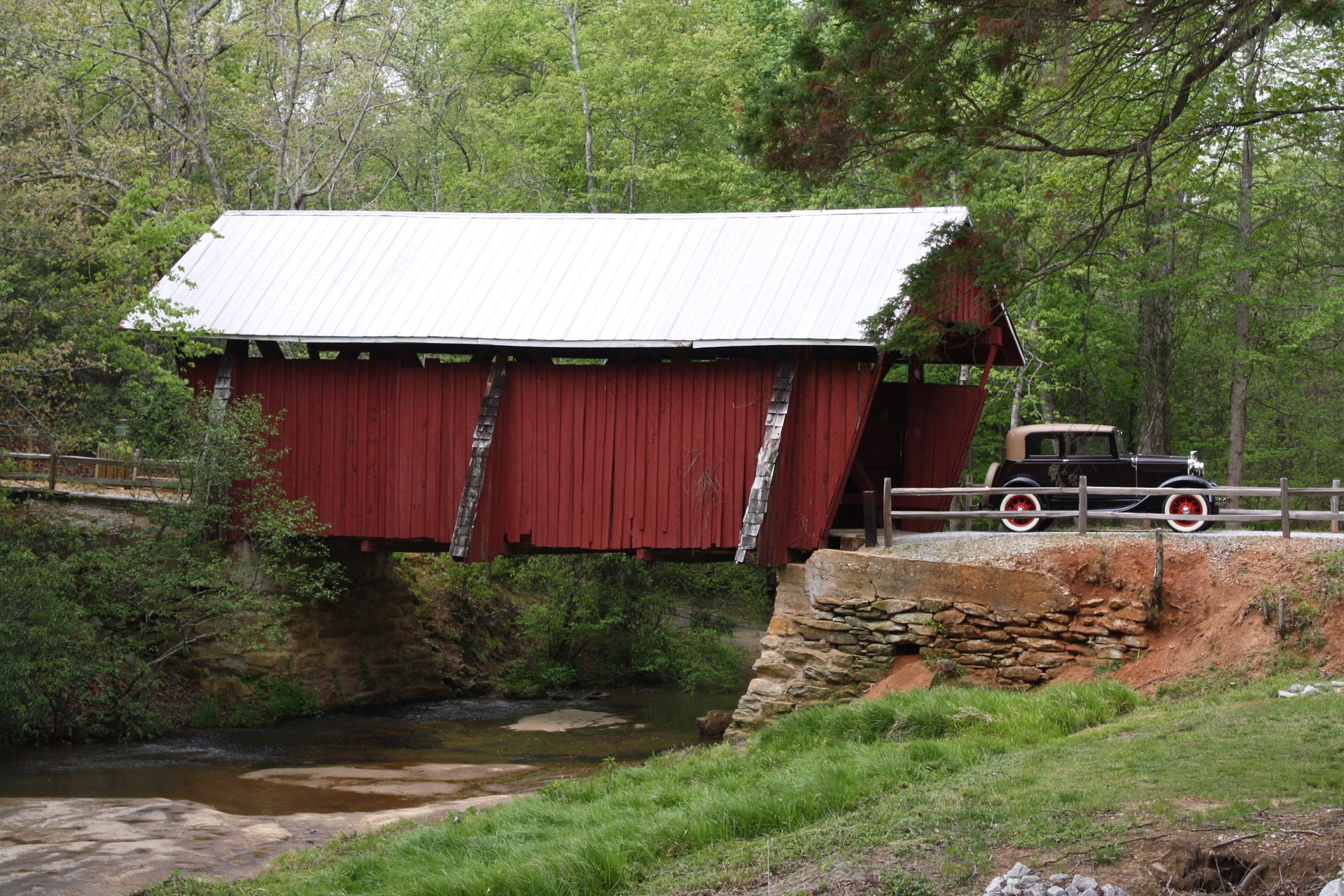 covered bridge with old time car driving through it