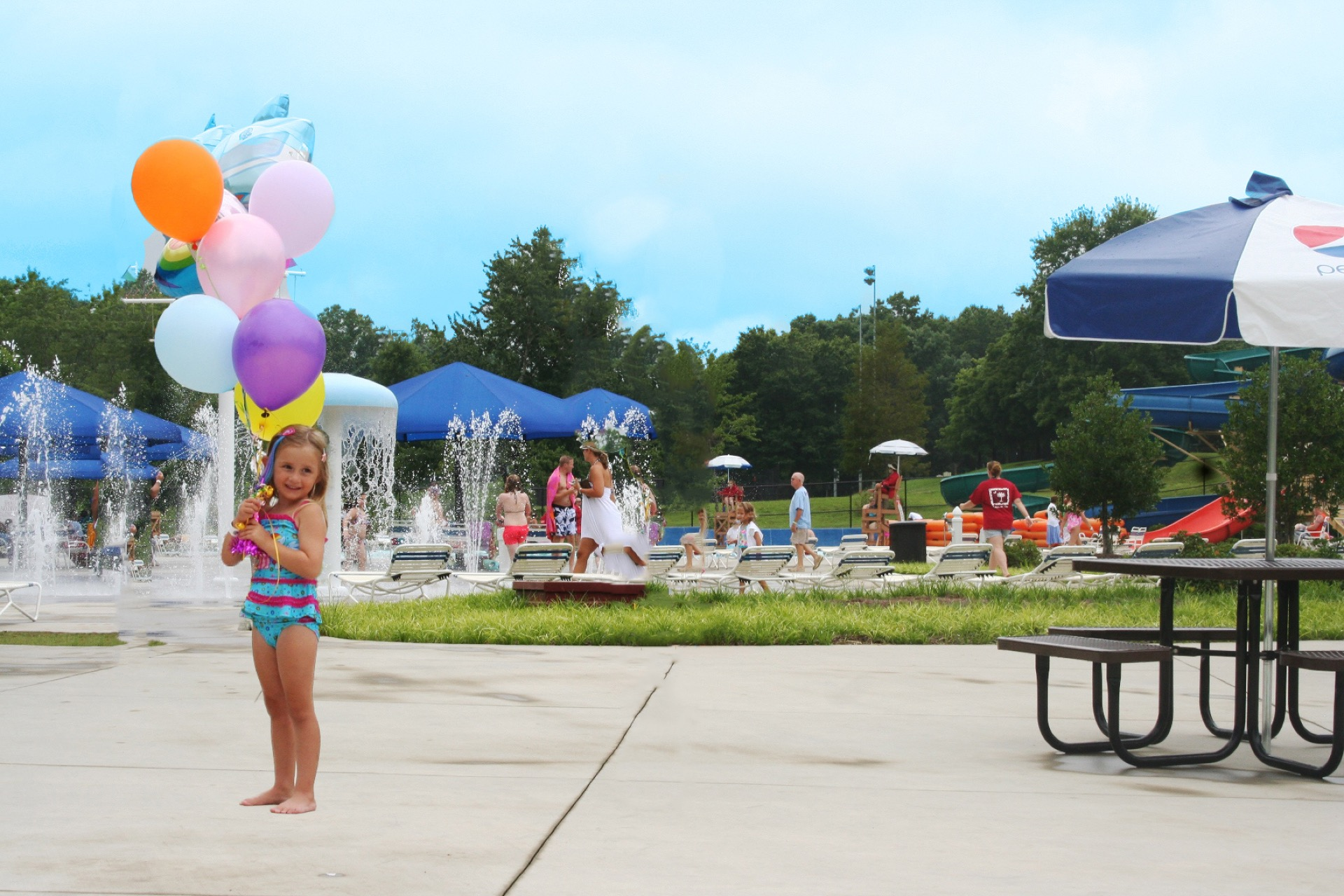 girl holding seven balloons at water park
