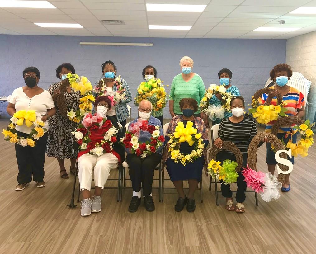 senior citizens holding hand made wreaths