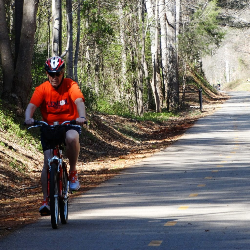 Man cycling on trail wearing orange shirt