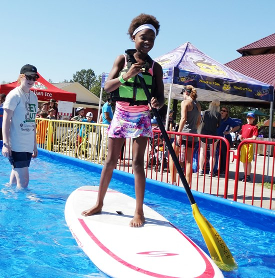 girl paddle boarding in Get Out pool