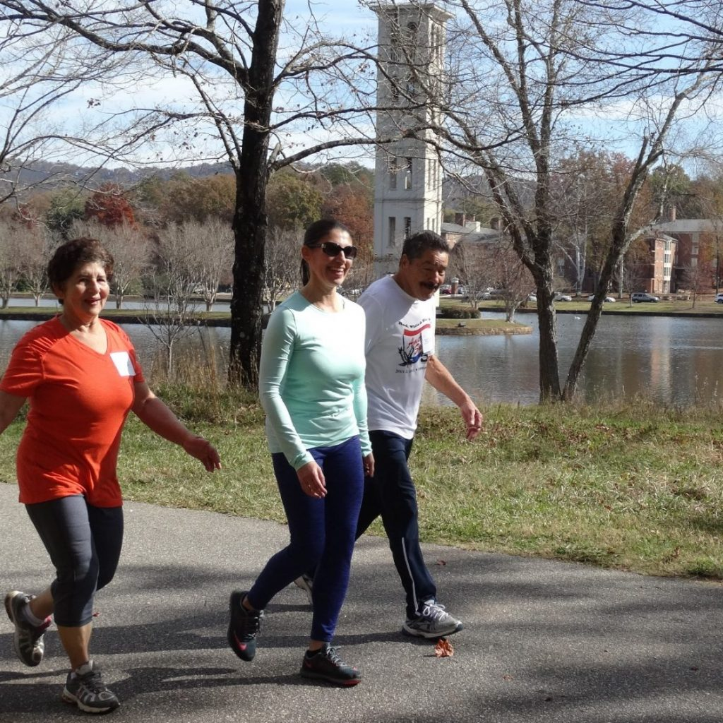adults walking on Furman campus in the fall