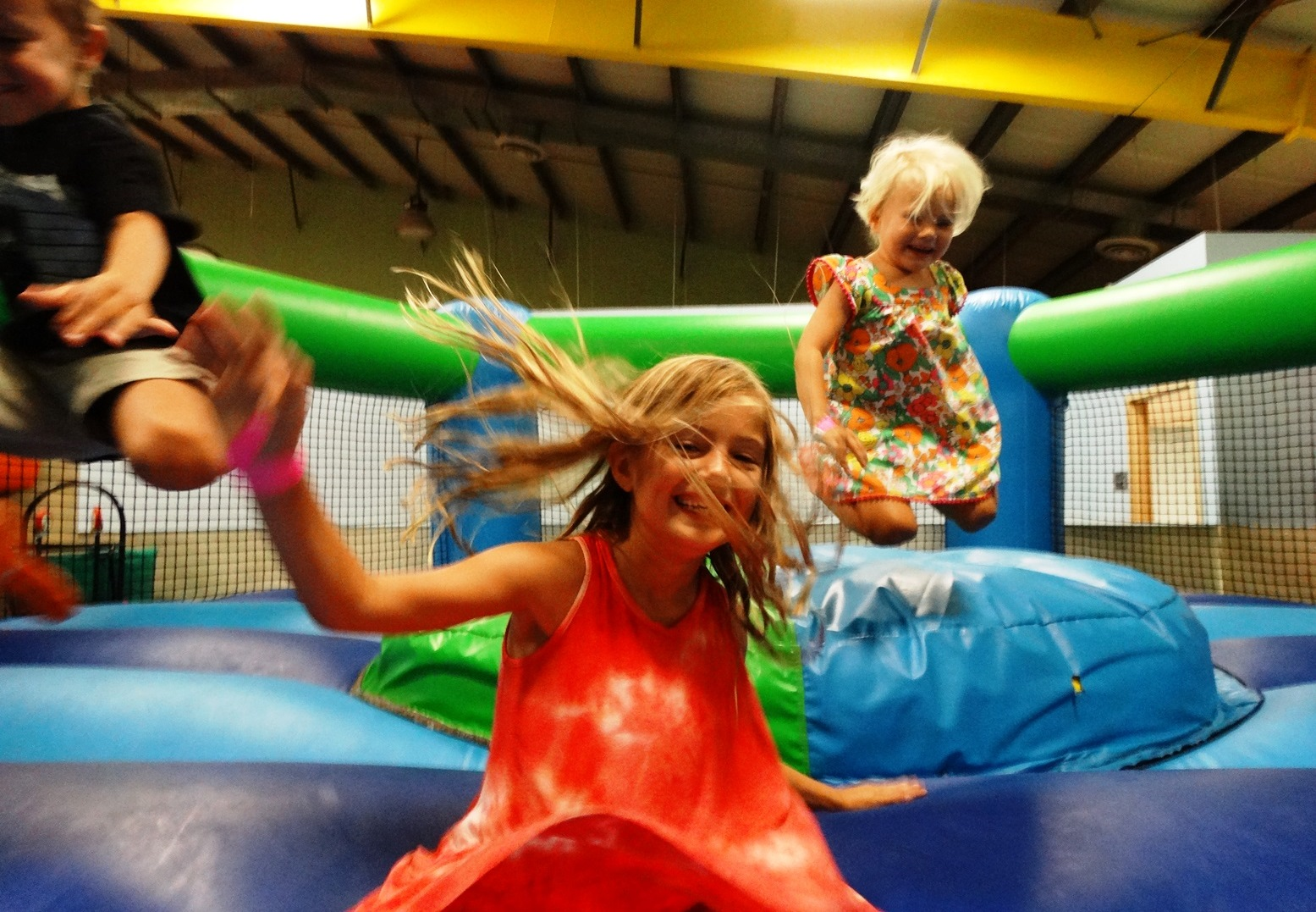 Three kids bouncing in bounce house