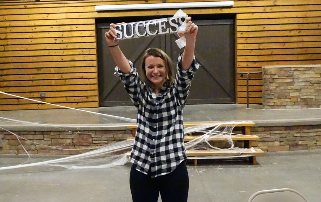 woman holds up success banner