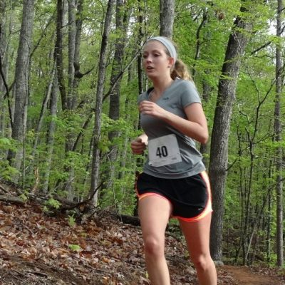 woman running trail in woods