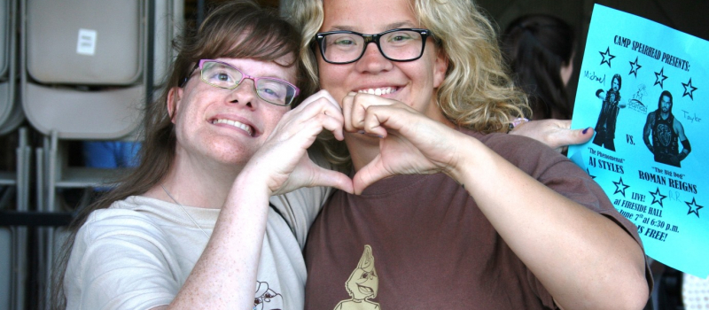 two female campers making a heart shape with their hands