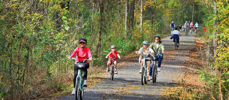 People enjoying riding on the trail in the fall