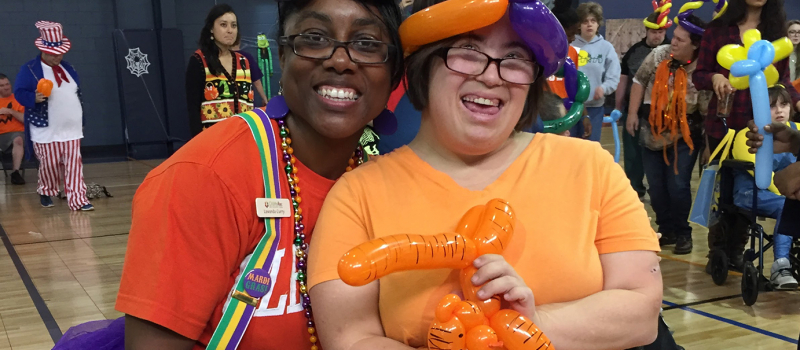volunteer and camper dressed in mardi gras costumes